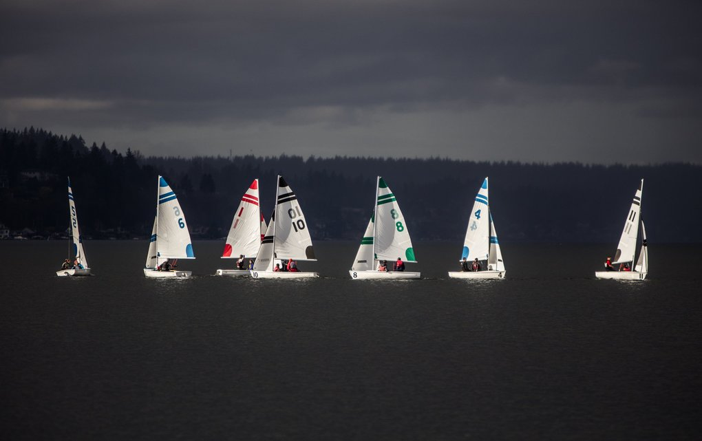 Tuesday, March 15, 2016. FJ sailboats cross paths while warming up for a High School sailing team practice on Lake Washington with looming clouds darkening the sky and water. Sailing out of the Sail Sand Point near Magnusen Park, the High School team practices for racing regattas throughout the Northwest. (Steve Ringman / The Seattle Times)